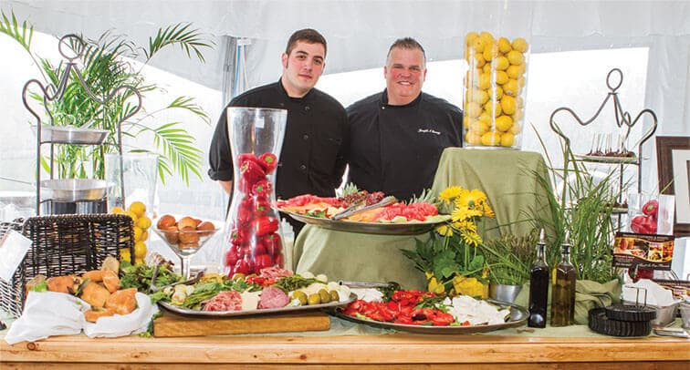 Chef Joe and an assistant in front of a gourmet spread.