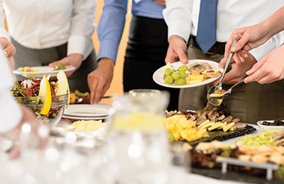 Employees getting for from a gourmet lunch spread