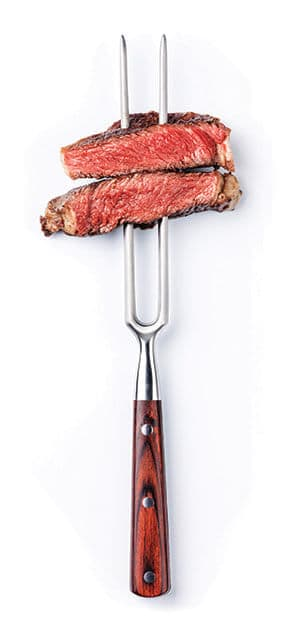 Fork with perfectly cooked beef on it.